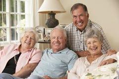 Groep Teruggetrokken Vrienden die op Sofa At Home Together zitten Stock Afbeelding