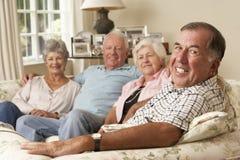 Groep Teruggetrokken Vrienden die op Sofa At Home Together zitten Royalty-vrije Stock Fotografie