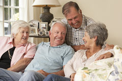 Groep Teruggetrokken Vrienden die op Sofa At Home Together zitten Stock Foto