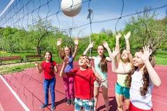 Groep tienerjaren die volleyball spelen dichtbij het net Royalty-vrije Stock Foto's