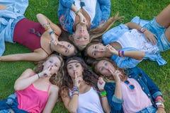 Groep tienerjarenvingers aan lippen voor verrassingsgeheim Stock Fotografie
