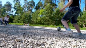 Groep tieners die na de voetbal van de bal speelwerf in de zomerdag in het park lopen stock footage