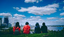 Groep tieners die op een heuvel zitten stock fotografie