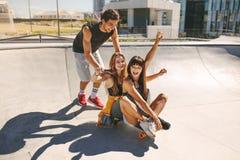 Groep tieners die in openlucht van met skateboard genieten stock foto