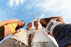 Groep tieners Jonge meisjes en jongens die en op een blauwe hemelachtergrond koesteren glimlachen Het concept van de vriendschap  Royalty-vrije Stock Foto's