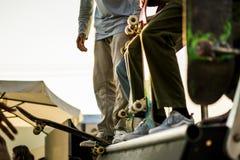 Groep tieners met hun skateboards op de helling die aan de concurrentie tijdens een zonsondergang deelnemen stock foto's