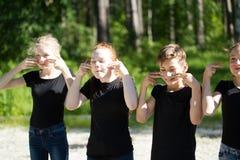 Groep tieners in zwarte t-shirts die hun gezichten schilderen die pret hebben in openlucht bij zonnige dag stock foto