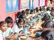 Groep tienersleerlingen die gediende Maaltijdplaat van rijst in de Kantine van de overheidsschool zijn Ongezond voedsel voor slec royalty-vrije stock foto