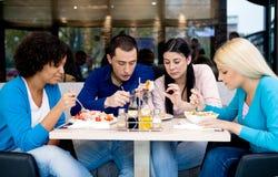 Groep tienersstudenten op lunch stock afbeeldingen