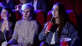 Groep tienervrienden bij de bioskoop die op een film letten en popcorn eten stock videobeelden