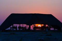 Groep toeristen die op kleurrijke zonsondergang letten onder schuilplaats Toeristentoevlucht in Afrika Backlight, silhouet, achte royalty-vrije stock afbeeldingen