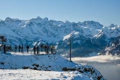 Groep toeristen en skiërs bovenop Fronalpstock dichtbij Stoos stock afbeelding