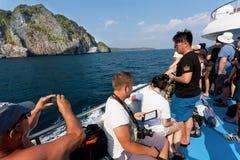 Groep toeristen op veerboot die naar tropisch eiland met klippen en duidelijk water gaan Royalty-vrije Stock Foto