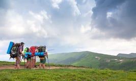 Groep toeristenwandelaars die zich in bergen bevinden die als hun beschouwen Royalty-vrije Stock Foto