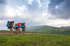Groep toeristenwandelaars met rugzakken die zich in bergen bevinden Royalty-vrije Stock Foto's