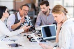 Groep uitvinders die apparaat in bureau testen Stock Afbeelding
