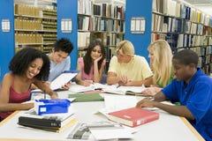 Groep universitaire studenten die in bibliotheek werken Stock Foto's
