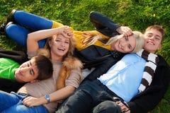 Groep van vier jonge mensen die in het gras leggen Stock Foto