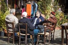 Groep van vier oude mannelijke vrienden die in stadspark spreken