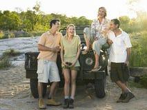Groep van Vier Vrolijke Mensen door Jeep stock afbeeldingen