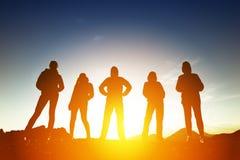 Groep van vijf volkeren in silhouetten bij zonsondergang royalty-vrije stock afbeelding