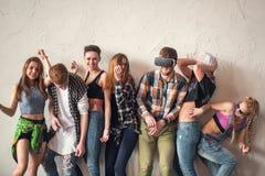 Groep van zeven vrienden die uit luide binnen, delend goede en positieve stemming lachen Makend partij binnen Stock Afbeelding