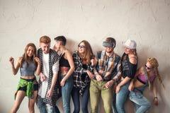 Groep van zeven vrienden die uit luide binnen, delend goede en positieve stemming lachen Makend partij binnen Royalty-vrije Stock Fotografie