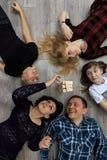 Groep verschillend vrienden, volwassenen en kind, het spel van spelbakstenen op vloer Stock Afbeeldingen