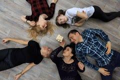 Groep verschillend vrienden, volwassenen en kind, het spel van spelbakstenen op vloer Royalty-vrije Stock Fotografie