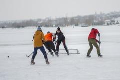 Groep verschillende oude mensen die hokey op een bevroren rivier Dnipro in de Oekraïne spelen stock foto