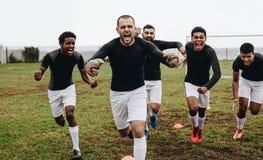 Groep voetbalsters die op gebied lopen die in vreugde na het noteren van een doel schreeuwen Spelers die overwinning vieren die o stock foto