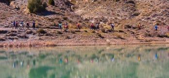 groep volwassen mensen met kleurrijke rugzaktrekking op een weg van zand en stenen die naast een meer lopen die op hun beelden wi stock foto's