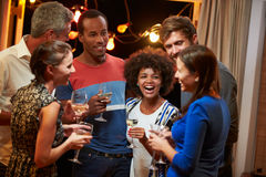 Groep volwassen vrienden die bij een huispartij drinken stock fotografie