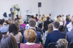 Groep Volwassenen die aan de Gastheer op Stadium tijdens een Conferentie luisteren Stock Foto