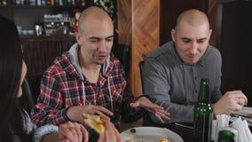 Groep vrienden bij de pizzeria De kerel met de rente vertelt het verhaal Pizza en bier stock video