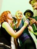 Groep vrienden bij karaokepartij Stock Foto's