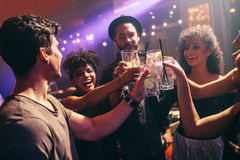 Groep vrienden bij nachtclub het vieren met dranken stock foto's