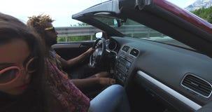 Groep vrienden die aan muziek in rode convertibel luisteren stock footage