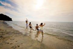Groep vrienden die bij het zonsondergangstrand springen Stock Afbeeldingen