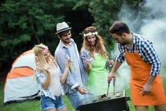 Groep vrienden die een barbecue samen in openlucht in de aard maken stock fotografie