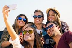 Groep vrienden die een selfie met smartphone nemen Stock Afbeelding