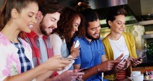 Groep vrienden die elkaar en mobiele telefoon met behulp van op elkaar inwerken
