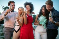 Groep vrienden die, en een pret drinken babbelen hebben bij openluchtpartij stock afbeeldingen