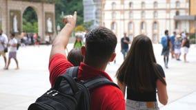 Groep vrienden die en toeristenplaats lopen onderzoeken Jonge mens die aan iets aan haar meisjes tijdens reis richten stock videobeelden