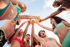 Groep vrienden die flessen samen clinking stock foto's