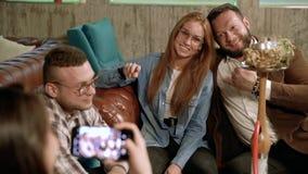 Groep vrienden die foto's nemen die een smartphone in een koffie gebruiken stock video