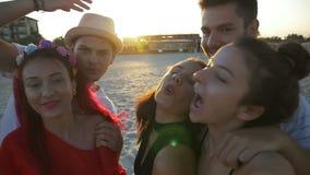 Groep vrienden die grappige gezichten op videovraag op het strand maken stock videobeelden