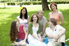 Groep vrienden die in het gras zitten Stock Foto