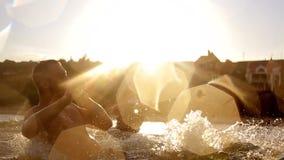 Groep vrienden die in het overzees bij zonsondergang zwemmen die nat en plonsen in langzame motie maken worden Jonge mensen die p stock video
