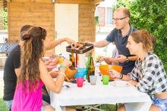 Groep vrienden die lunch samen in de tuin hebben Stock Afbeelding